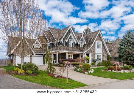 Beautiful exterior of newly built luxury home. Yard with green grass and stones