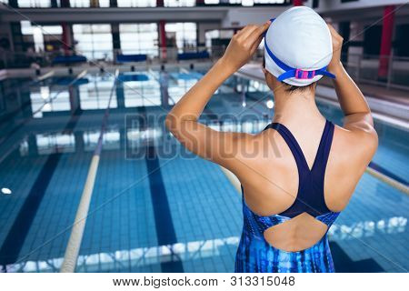 Rear view of a young African-American woman wearing a swimsuit and swimming cap with goggles while standing by an olympic sized pool inside a stadium
