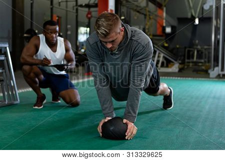 Front view of handsome fit African-american male trainer writing on clipboard while young Caucasian male athletic exercising with exercise ball in fitness center. Bright modern gym with fit healthy