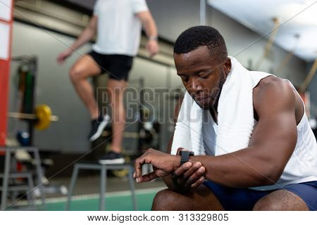 Front view of handsome young African-american male athletic checking time on watch in fitness center. In the background Caucasian male athletic is exercising. Bright modern gym with fit healthy people