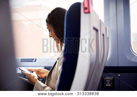 Businesswoman Sitting In Train Commuting To Work Checking Messages On Mobile Phone