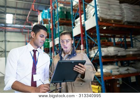 Front view of diverse staffs discussing over digital tablet in warehouse. This is a freight transportation and distribution warehouse. Industrial and industrial workers concept