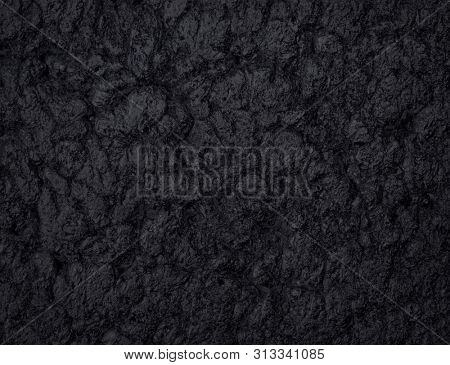 Natural black stone texture for backgrounds. Top view