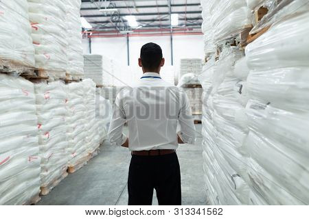 Rear view of thoughtful Caucasian male supervisor standing in warehouse. This is a freight transportation and distribution warehouse. Industrial and industrial workers concept poster
