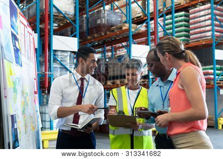 Front view of diverse warehouse staffs discussing over clipboard in warehouse. This is a freight transportation and distribution warehouse. Industrial and industrial workers concept