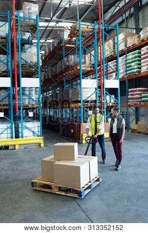 Front view of Caucasian Male staff with his Caucasian female coworker using pallet jack in warehouse. This is a freight transportation and distribution warehouse. Industrial and industrial workers
