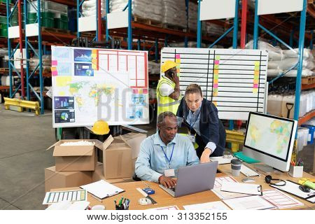 Front view of mature Caucasian female manager and African-american male supervisor discussing over laptop at desk in warehouse. This is a freight transportation and distribution warehouse. Industrial