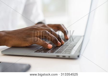Close up of african business man hands working using keyboard of computer laptop