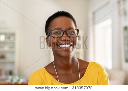Portrait of young woman at home wearing spectacles. Beautiful mature woman wearing eyeglasses and looking at camera. Cheerful african american lady with glasses and short hair.