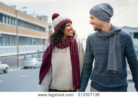 Casual young couple holding hands while walking on the street. Happy couple wearing winter clothes and looking at each other. Romantic multiethnic man and woman enjoying winter breeze outdoor.