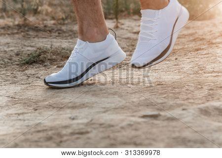 Men's Feet In White Sneakers Running Over Rough Terrain. Cross Country Running With Focus On Runner'