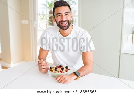 Handsome hispanic man eating healthy breakfast in the morning at home with a happy face standing and smiling with a confident smile showing teeth