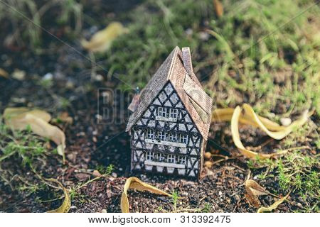 A Small Model Of A Half Timber House On The Ground