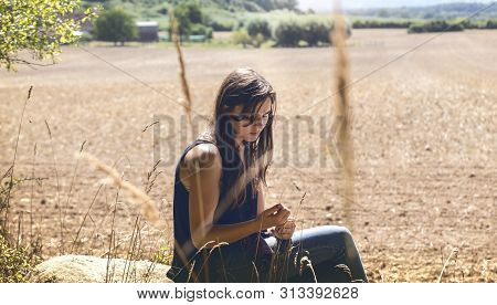 Portrait Of A Thoughtful Sad Young Woman Sitting On A Rock