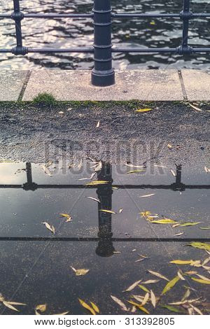 Railing Of A Canal Mirroring In A Puddle With Autumn Leaves