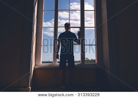 Young Man Standing In A Dark Room In Front Of A Window
