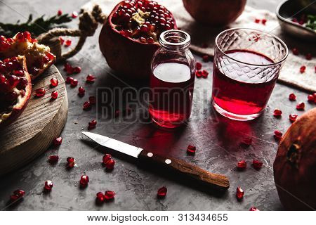 Red Pomegranate Juice In A Glass, Ripe And Cut Pomegranate And A Sprig Of Mint On A Gray Concrete Ba