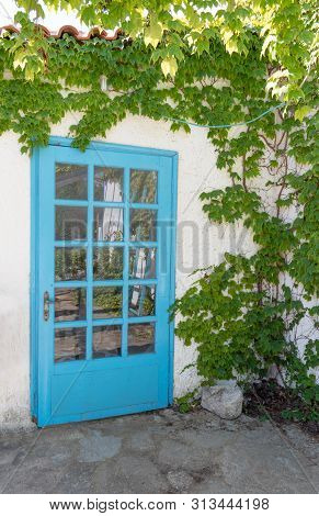 Facade Of Traditional White Greek House With Blue Door And Window And Reflected On Glass Stock Photo