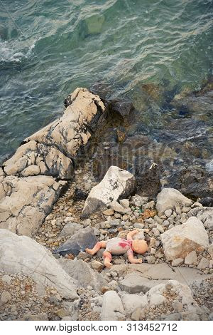 Morbid View Of An Abandoned Baby Doll Covered In Red Paint Lying On The Stones Of A Rocky Beach. Neg