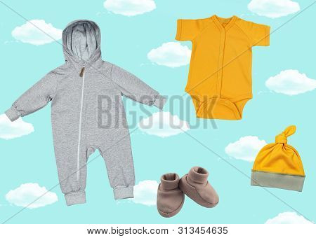 Bright Collage With Clothes For Newborn Babies On A Blue Background With Clouds.