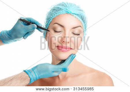 Lower Eyelid Plastic Surgery Concept. Doctor Hands Drawing Marks On Female Face Isolated On White Ba