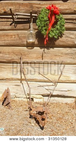 Christmas Wreath Hanging On Old Barn With Rusty Tools