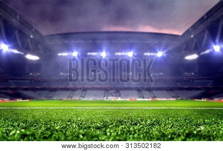 Stadium With Green Soccer Field And Bright Spotlights At Night
