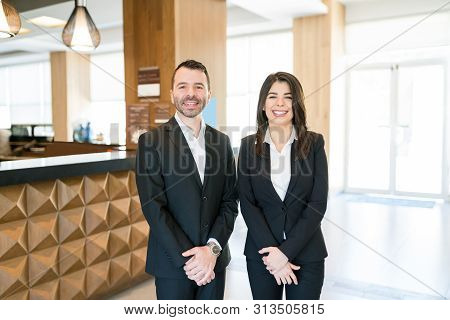 Confident Attractive Male And Female Managers Smiling While Making Eye Contact Against Reception Des