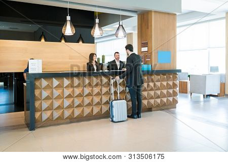 Businessman Making Booking At Front Desk With Latin Receptionists In Hotel Lobby