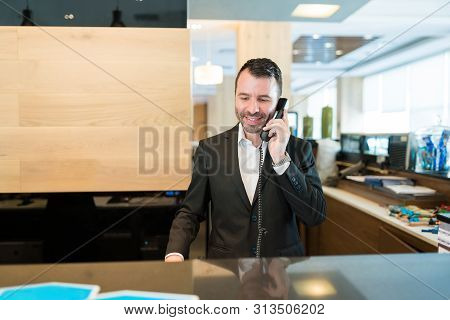 Happy Male Receptionist Confirming Booking While Talking On Phone At Front Desk In Hotel
