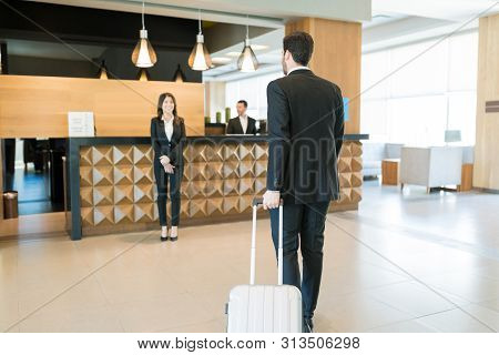 Full Length Of Happy Manager Awaiting For Ceo On Business Trip Arriving At Front Desk In Hotel