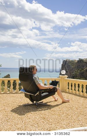 Man Working On His Laptop From Vacation