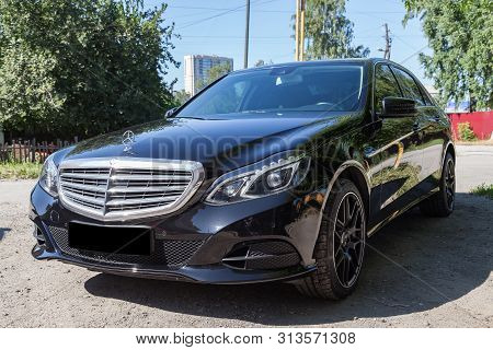 Novosibirsk, Russia - 07.20.2019: Black Mercedes Benz E-class E350 2013 Year Front View With Dark Gr