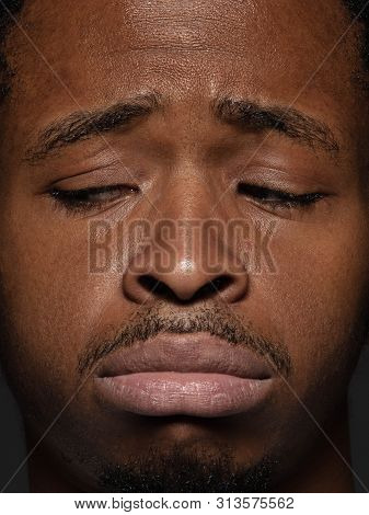 Close up portrait of young and emotional african-american man. Highly detail photoshot of male model with well-kept skin and facial expression. Concept of human emotions. Upset, sad, demotivated. poster