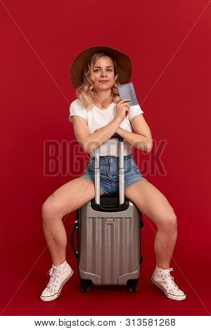 Happy Young Woman With Blod Curly Hair In A Sundown Hat Sits On A Grey Luggage Bag Holding Passport