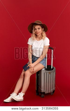 Smiling Young Woman With Blod Curly Hair In A Sundown Hat Sits On A Grey Luggage Bag Holding Passpor