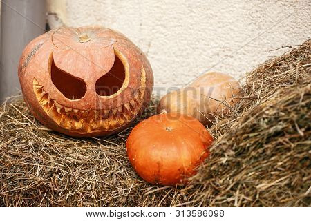 Halloween Street Decor. Jack O Lantern Pumpkins On Hay In City Street, Holiday Decor Of Store Fronts