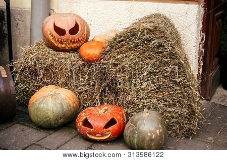 Pumpkins With Scary Faces On Hay In City Street, Holiday Decoration Of Store Fronts And Buildings. H