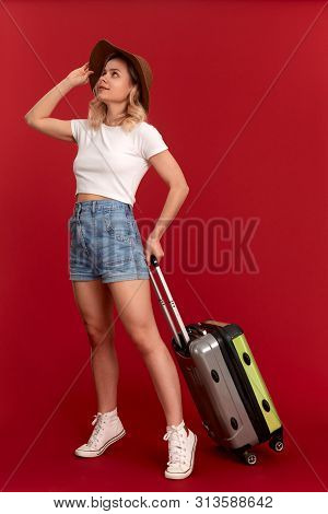 Young blond curly woman in a sundown hat with grey luggage bag is excited at sightseeing tour while standing infront of a red background. Concept of traveling poster