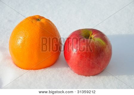 The image of apple and orange on snow
