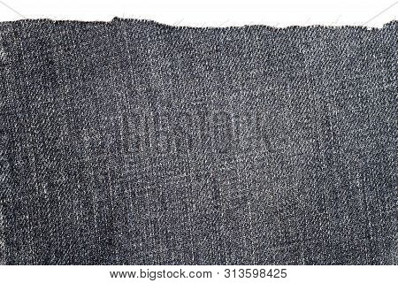 Piece of dark jeans fabric isolated on white background. Rough uneven edges. poster