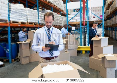 Front view of handsome mature Caucasian male supervisor writing on clipboard in warehouse. Diverse workers checking stock in cardboard boxes behind supervisor. This is a freight transportation and