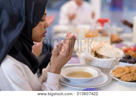 modern black muslim woman praying before having iftar dinner together with multiethnic family during a ramadan feast at home