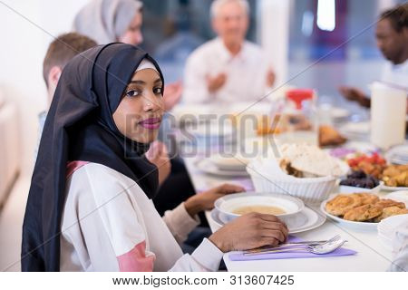 modern african american muslim woman enjoying iftar dinner together with multiethnic family during a ramadan feast at home