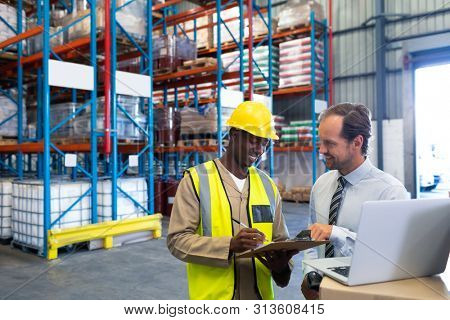 Front view of happy diverse staffs discussing over clipboard in warehouse. This is a freight transportation and distribution warehouse. Industrial and industrial workers concept