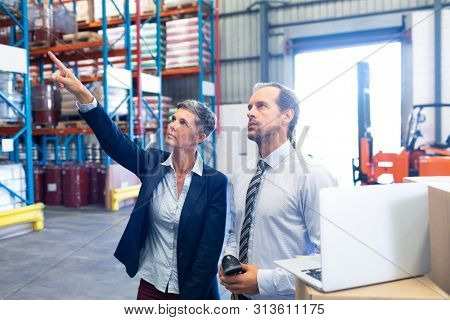 Front view of beautiful mature Caucasian female manager standing with Caucasian male supervisor and pointing at distance in warehouse. This is a freight transportation and distribution warehouse.