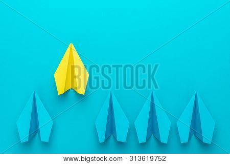 Top View Of Yellow Paper Plane As Out Of The Crowd Concept Over Turquoise Blue Background With Copy