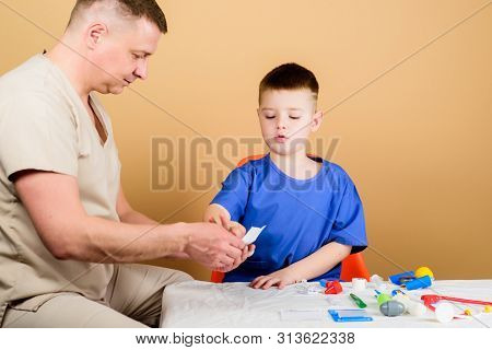 Kid Little Doctor Sit Table Medical Tools. Health Care. Medical Examination. Boy Cute Child And His