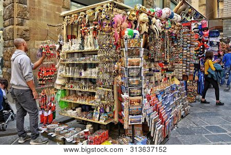 Man Searches A Souvenir. Street Market In Italy. Market Stall With Venice Carnival Masks, Figurines,