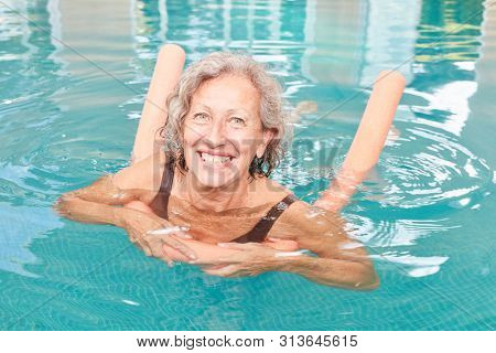 Vital senior woman learns swimming in the swimming pool with a swim noodle